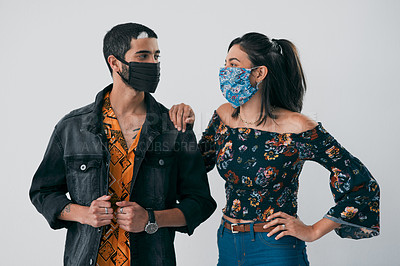 Buy stock photo Studio shot of a masked young man and woman posing against a grey background