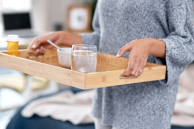 Buy stock photo Shot of an unrecognisable woman serving breakfast in bed while to someone recovering from an illness at home