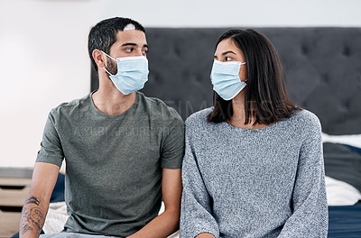 Buy stock photo Shot of a masked young couple recovering from an illness in bed at home