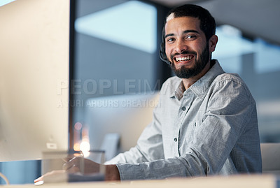 Buy stock photo Shot of a young man using a headset and computer late at night in a modern office