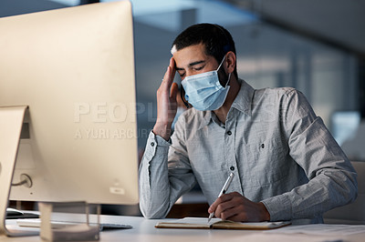 Buy stock photo Shot of a masked young man feeling stressed while using a headset and computer late at night in a modern office