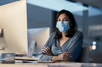 Buy stock photo Shot of a masked young woman using a headset and computer late at night in a modern office