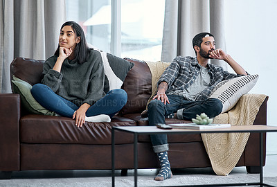 Buy stock photo Shot of a young couple sitting on the sofa and ignoring each other