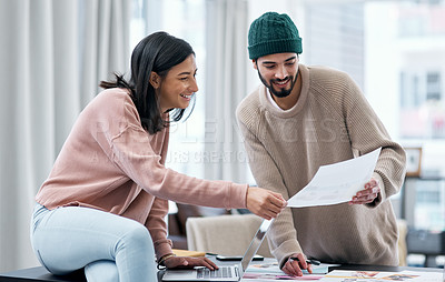 Buy stock photo Shot of a young man and woman using a laptop and going though paperwork while working from home