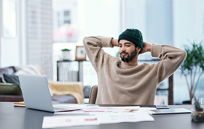 Buy stock photo Shot of a young man taking a break while working from home