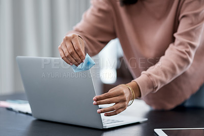 Buy stock photo Shot of an unrecognisable woman disinfecting her laptop while working from home