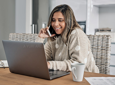 Buy stock photo Shot of a woman talking on her cellphone and using her laptop while working from home
