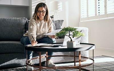 Buy stock photo Shot of a young woman looking at paperwork while working from home