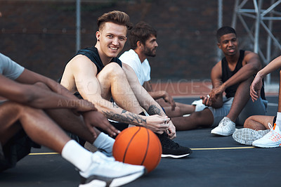 Buy stock photo Shot of a sporty young man hanging out with his friends on a basketball court
