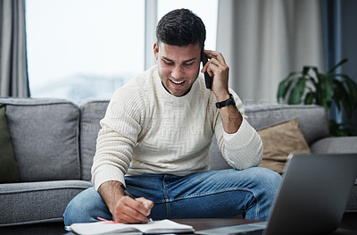 Buy stock photo Shot of a young man using a laptop and smartphone while writing in a notebook at home