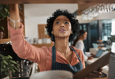 Buy stock photo Shot of a woman counting stock while working in a cafe