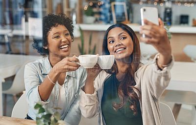 Buy stock photo Shot of two friends taking a selfie while sitting together in a coffee shop