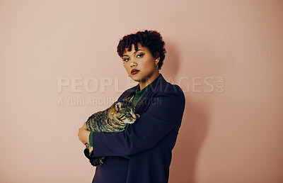 Buy stock photo Shot of a beautiful young woman holding her cat while posing against a plain background