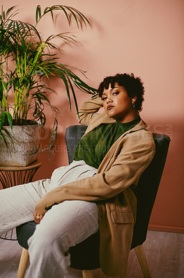 Buy stock photo Shot of a fashionable young woman sitting on a chair in the living room