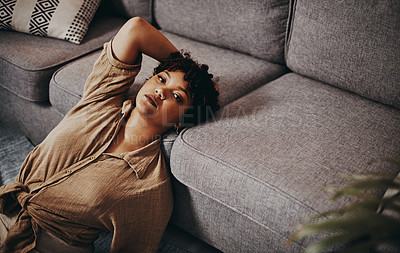 Buy stock photo Shot of a beautiful young woman relaxing on the floor in the living room