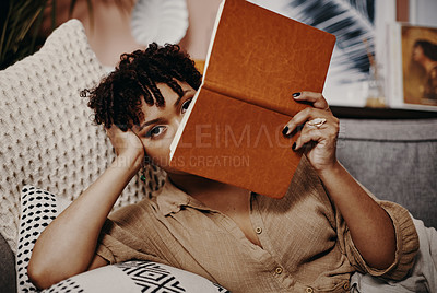 Buy stock photo Shot of a young woman holding a book over her face while relaxing at home