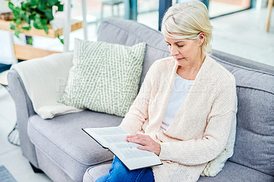 Buy stock photo Shot of a senior woman reading a book on the sofa at home