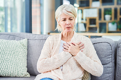 Buy stock photo Shot of a senior woman suffering from chest pain while sitting on the sofa at home