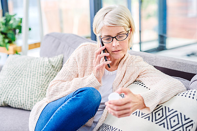 Buy stock photo Shot of a senior woman using a smartphone and reading the label on a medicine container at home