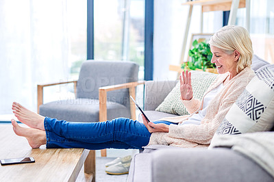 Buy stock photo Shot of a senior woman using a digital tablet to make a video call on the sofa a home