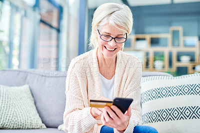 Buy stock photo Shot of a senior woman using a smartphone and credit card on the sofa at home