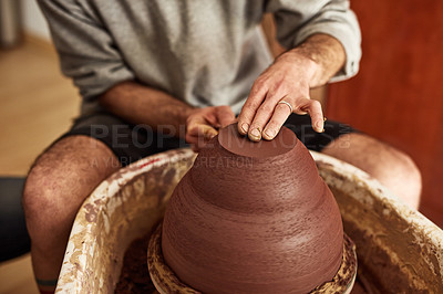 Buy stock photo Shot of an unrecognisable man working with clay in a pottery studio