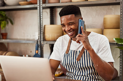 Buy stock photo Shot of a young man using a laptop and smartphone while working in a ceramic studio