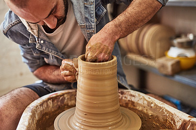 Buy stock photo Shot of a young man working with clay in a pottery studio