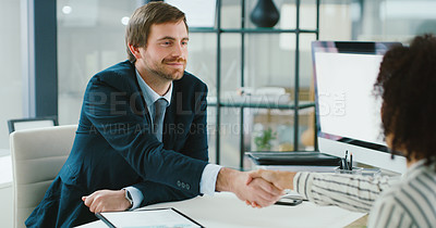 Buy stock photo Shot of a young businessman and businesswoman shaking hands in a modern office
