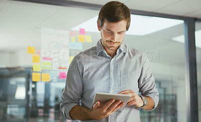Buy stock photo Shot of a young businessman using a digital tablet while having a brainstorming session in a modern office