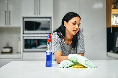 Buy stock photo Shot of a young woman looking bored while doing chores at home