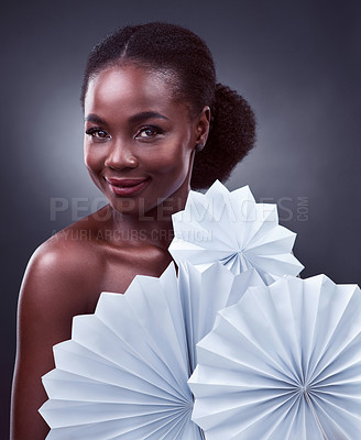 Buy stock photo Studio portrait of a beautiful young woman posing with origami fans against a black background
