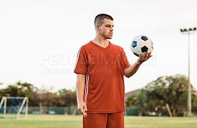 Buy stock photo Shot of a soccer player holding a ball while out on the field