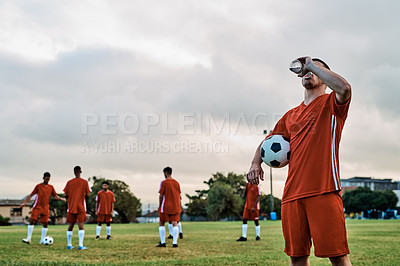 Buy stock photo Shot of a soccer player drinking water while out on the field