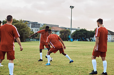 Buy stock photo Shot of a group of young soccer players practising on the field