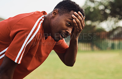Buy stock photo Shot of a soccer player looking exhausted while out on the field
