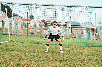 Buy stock photo Shot of a goalkeeper standing in front of a goalpost
