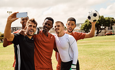 Buy stock photo Shot of young soccer players taking a selfie while standing together on the field