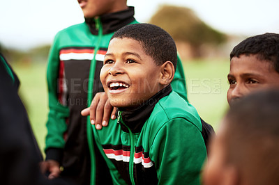 Buy stock photo Shot of a young boy standing alongside his soccer team on a sports field