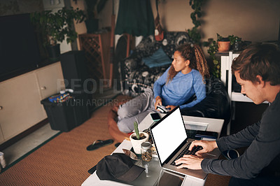 Buy stock photo Shot of a young woman playing video games while her boyfriend uses a laptop at home