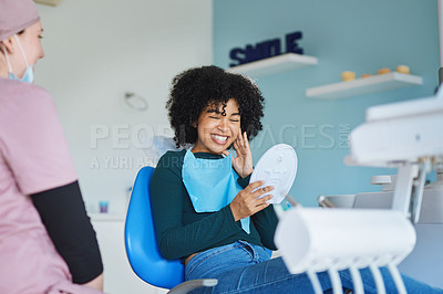 Buy stock photo Shot of a young woman admiring her teeth after having a dental procedure done