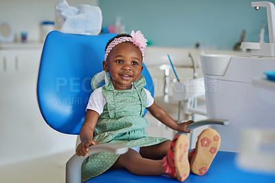 Buy stock photo Shot of an adorable little girl sitting in a dentist's chair