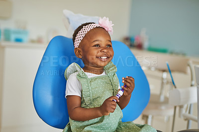 Buy stock photo Shot of an adorable little girl brushing her teeth in a dentist's chair