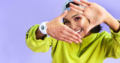 Buy stock photo Studio shot of a beautiful young woman making a finger frame gesture against a purple background