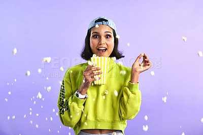 Buy stock photo Studio shot of a beautiful young woman eating popcorn against a purple background