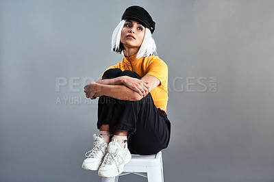 Buy stock photo Studio shot of a beautiful young woman sitting on a stool against a grey background