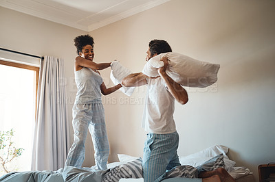 Buy stock photo Shot of a couple enjoying a pillow fight in their bedroom
