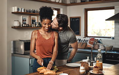Buy stock photo Shot of a man kissing his wife while she prepares breakfast in the kitchen at home
