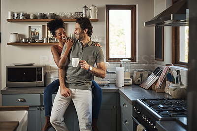 Buy stock photo Shot of an affectionate couple smiling at each other while spending quality time in their kitchen at home