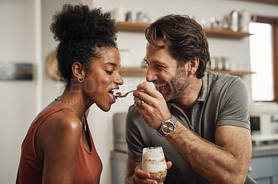 Buy stock photo Shot of a man feeding his wife while sitting together in their kitchen